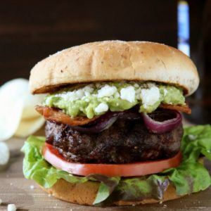 Bacon Guacamole Burgers with Grilled Onions and Cotija Cheese | completelydelicious.com