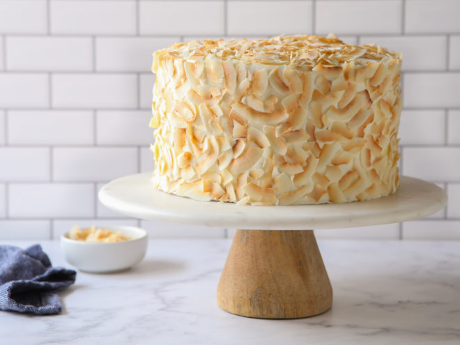 frosted southern coconut cake on a cake stand