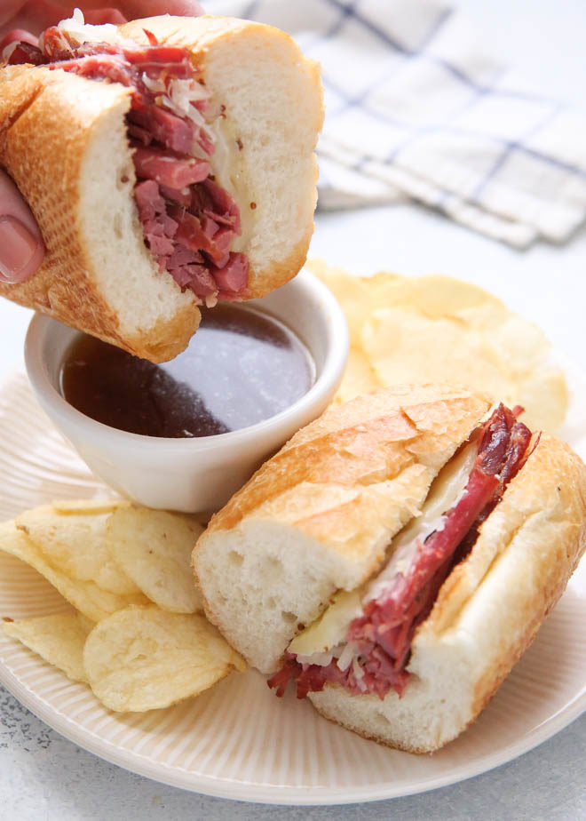 Dipping corned beef french dip sandwiches in au jus