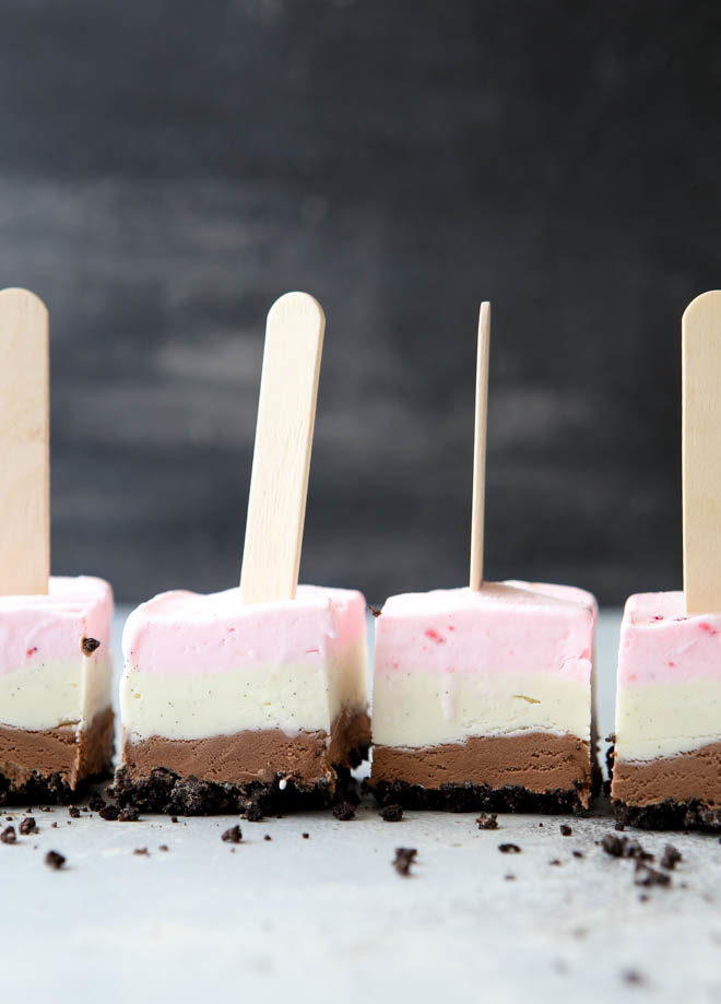 Layers of oreo cookie, chocolate ice cream, vanilla ice cream, and strawberry ice cream make up these fun Neapolitan ice cream pops