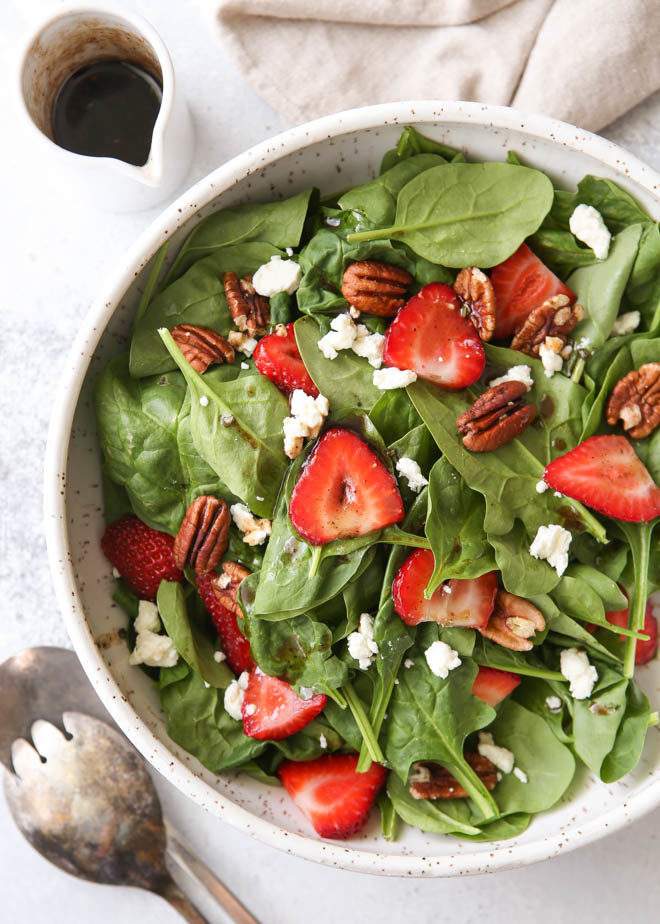 Strawberry spinach salad with warm brown butter dressing, toasted pecans, and feta cheese