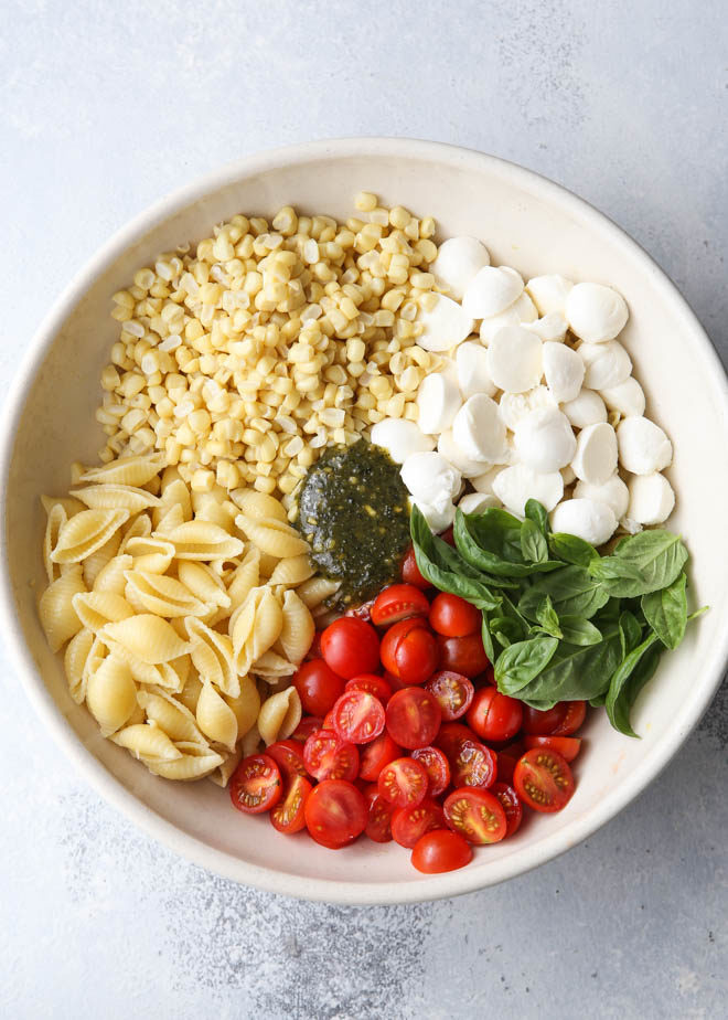 Making fresh corn, tomatoes, pesto and mozzarella salad