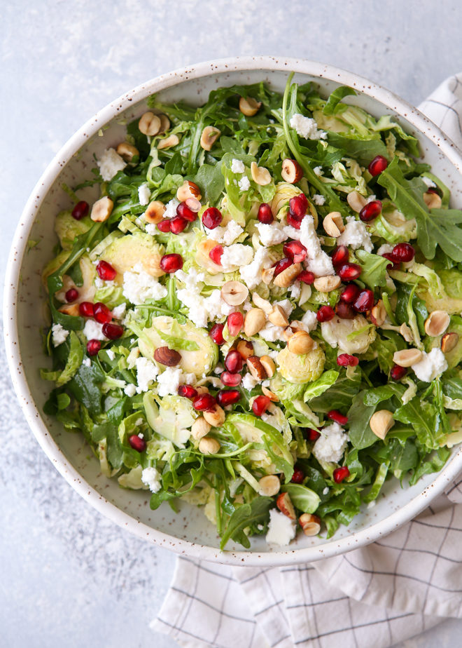 Shredded Brussels sprouts and arugula salad with feta, hazelnuts and pomegranate
