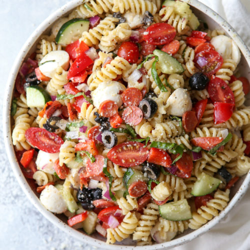 This quick and flavorful Italian pasta salad is filled with pepperoni, fresh mozzarella, bell peppers, tomatoes, cucumbers, olives and basil is perfect for potlucks and parties!