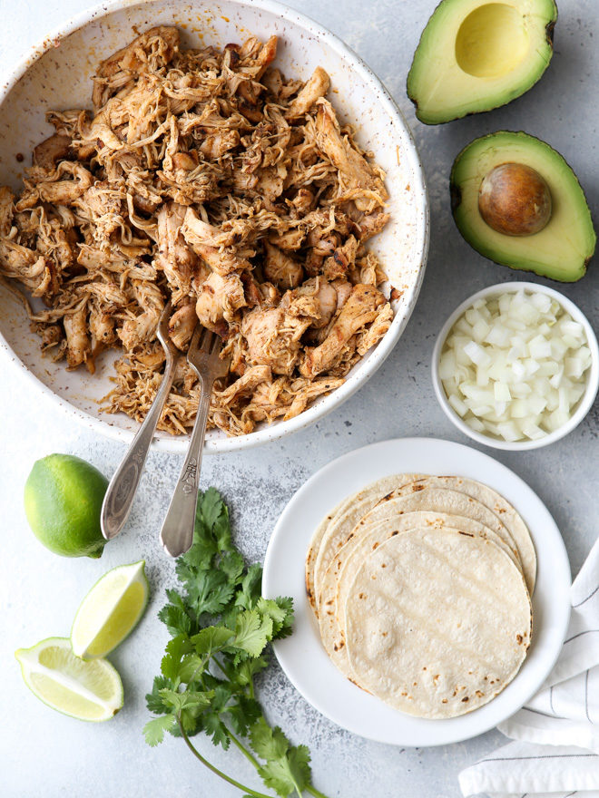 Serve shredded chicken street tacos with chopped onions, avocado, and fresh cilantro