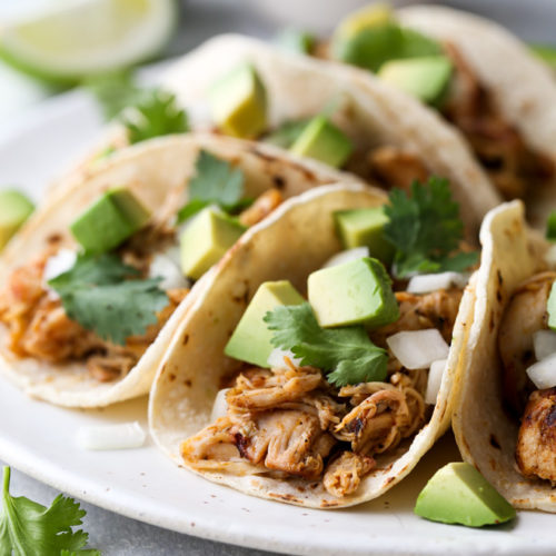 These easy Mexican street tacos filled with spiced shredded chicken, chopped onions, avocado, and cilantro are sure to become a favorite with everyone!