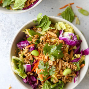 This Asian ramen cabbage salad is filled with napa and purple cabbage, shredded carrots, scallions, shelled edamame, crunchy ramen noodles, slivered almonds and a peanut sesame dressing.