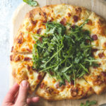 This simple but irresistible three-cheese white pizza is topped with crispy bacon and fresh arugula for maximum flavor.