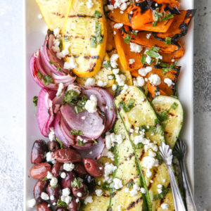This grilled vegetable antipasto platter of zucchini, summer squash, red onion, bell peppers caramelized on the grill and served with kalamata olives, goat cheese and basil dressing is exactly what your next summer dinner party needs!
