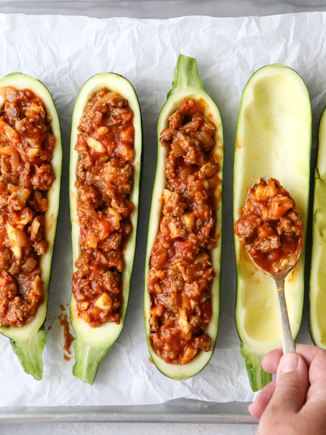Making sausage stuffed zucchini boats