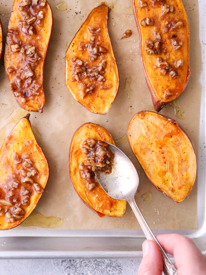Adding maple pecan sauce to the roasted sweet potatoes