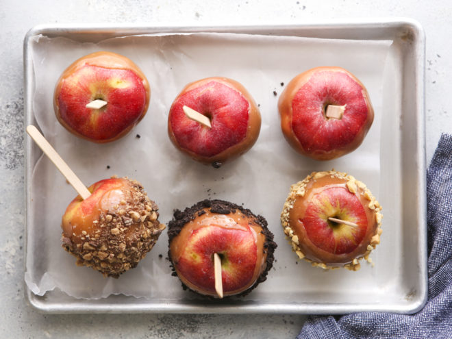 caramel apples with toppings on wax paper