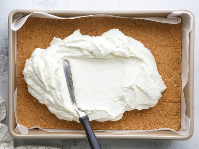 spreading filling over graham cracker crust