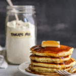 stack of pancakes on a plate with jar of buttermilk pancake mix in background